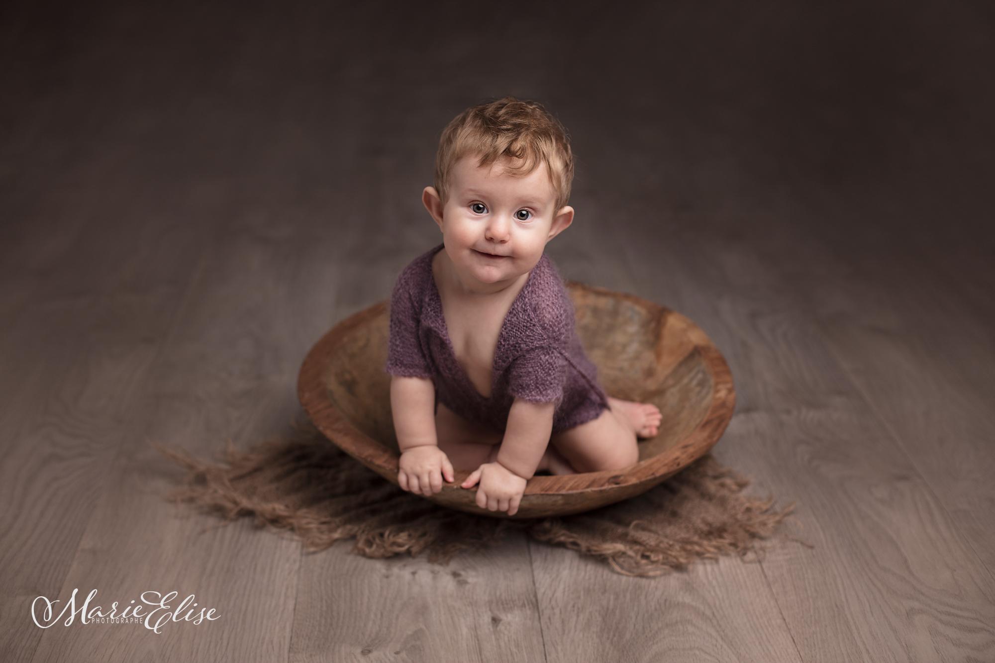 Bébé assis dans un bol en bois